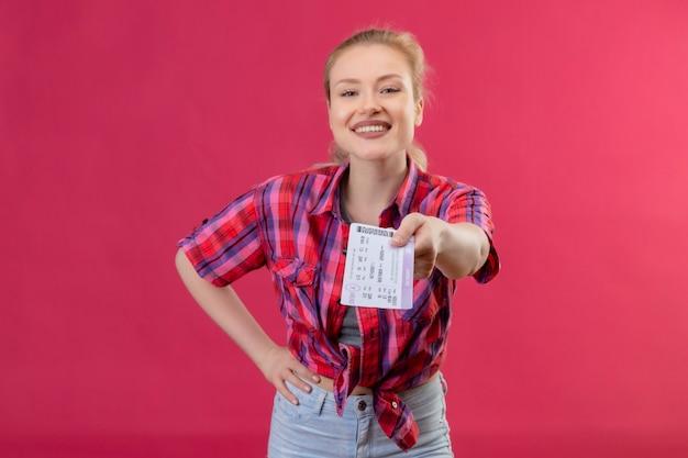Souriant voyageur jeune fille portant une chemise rouge tendu à des billets de caméra sur fond rose isolé
