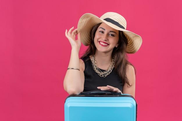 Souriant voyageur jeune fille portant un maillot de corps noir au chapeau a mis sa main sur le chapeau sur fond rouge