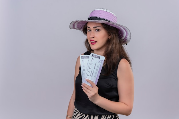 Souriant voyageur jeune fille portant un maillot de corps noir au chapeau tenant des billets sur fond blanc