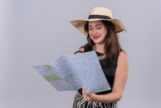 Souriant voyageur jeune fille portant un maillot de corps noir en chapeau tenant une carte sur fond blanc