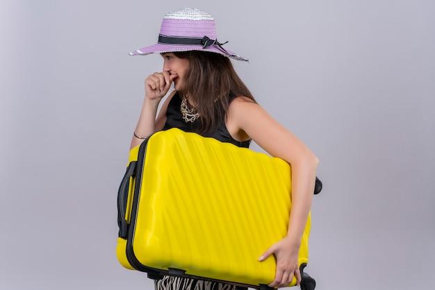 Souriant voyageur jeune fille portant un maillot de corps noir en chapeau tenant valise sur fond blanc