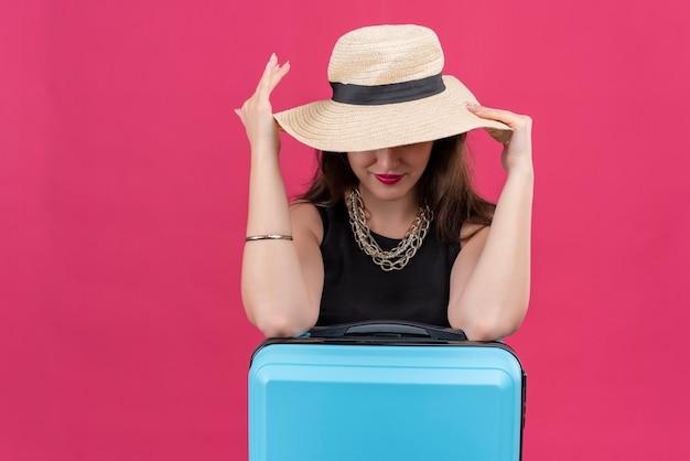 Souriant voyageur jeune fille portant un maillot de corps noir a mis les mains sur un chapeau sur fond rouge
