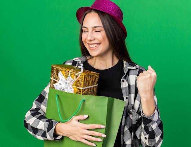 Souriant avec les yeux fermés jeune belle fille portant un chapeau de fête tenant un sac-cadeau montrant un geste oui