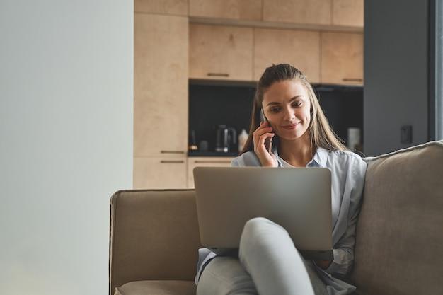 Souriante agréable jeune femme indépendante caucasienne blonde moderne avec un ordinateur portable assis sur le canapé