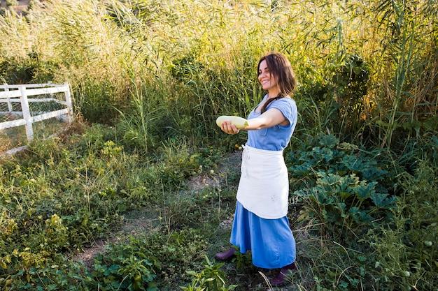 Souriante agricultrice montrant la gourde à la main