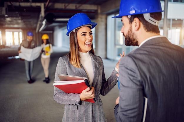 Souriante architecte féminine positive attrayante parlant à son superviseur d'idées pour la décoration intérieure. bâtiment à l'intérieur du processus de construction.