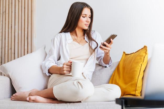 Souriante belle blonde en chemise blanche est assise sur un canapé blanc, parlant sur smartphone, tenant une tasse de café.