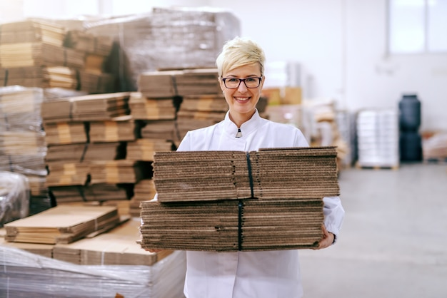 Souriante belle femme blonde relocalisant des boîtes de démontage en entrepôt.