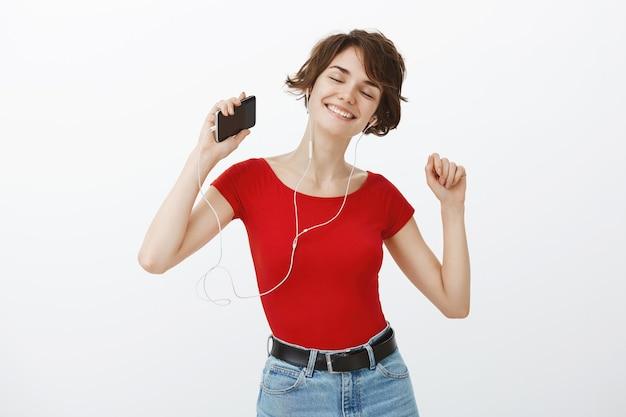 Souriante belle femme brune danse insouciante, écoute de la musique et danse dans les écouteurs, tenant le smartphone