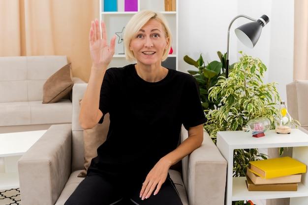 Souriante belle femme russe blonde est assise sur un fauteuil en levant la main à l'intérieur du salon