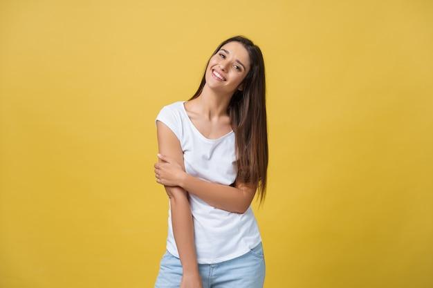 Souriante belle jeune femme en chemise blanche à la recherche d'appareil photo. studio de trois quarts de longueur tourné sur fond jaune.