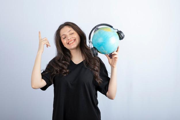 Souriante belle jeune femme debout et tenant un globe dans les écouteurs.