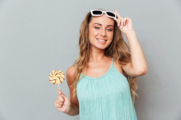 Souriante belle jeune femme à lunettes de soleil avec sucette sucrée sur mur gris