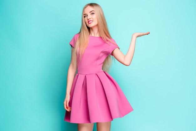 Souriante belle jeune femme en mini robe rose posant, présentant quelque chose