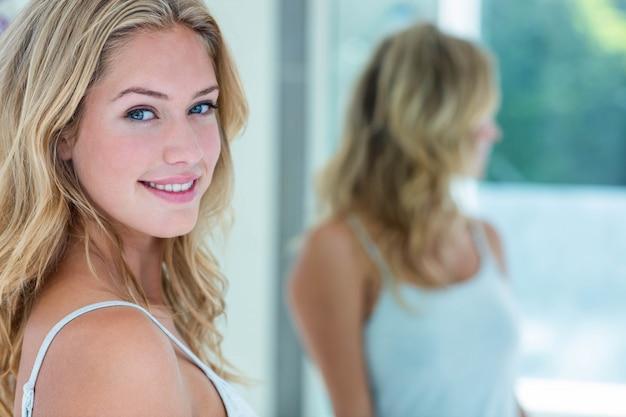 Souriante belle jeune femme se regardant dans le miroir de la salle de bain à la maison