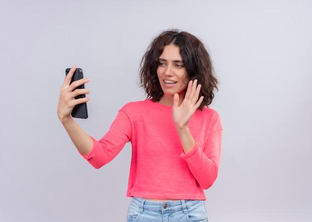 Souriante belle jeune femme tenant un téléphone mobile et en agitant sur un mur blanc isolé