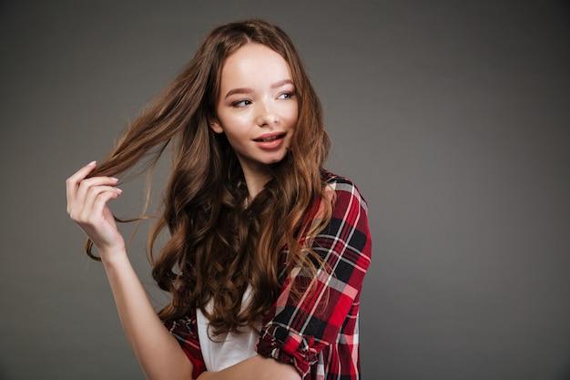 Souriante belle jeune femme toucher ses cheveux et regarder ailleurs