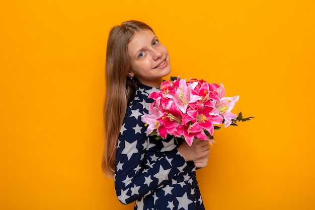 Souriante belle petite fille le jour de la femme heureuse tenant un bouquet isolé sur un mur orange