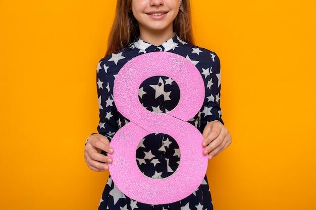 Souriante belle petite fille le jour de la femme heureuse tenant le numéro huit à la caméra isolée sur le mur orange