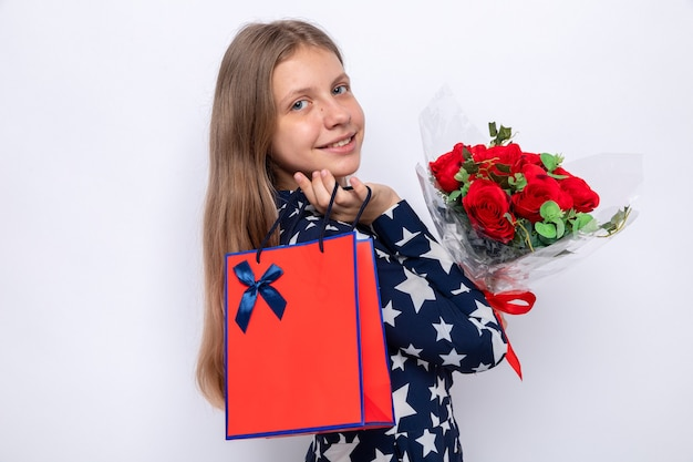 Souriante belle petite fille tenant un bouquet avec un sac cadeau