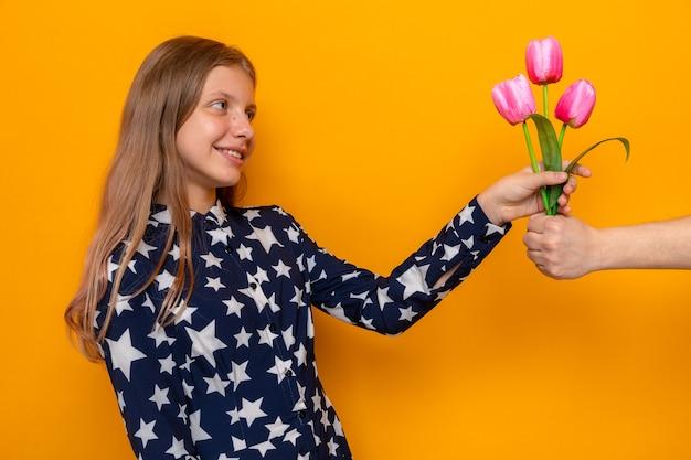 Souriante belle petite fille tenant le jour du bouquet donne des fleurs par quelqu'un