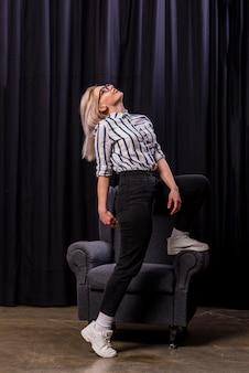 Souriante blonde jeune femme portant des lunettes en levant son pied sur un fauteuil