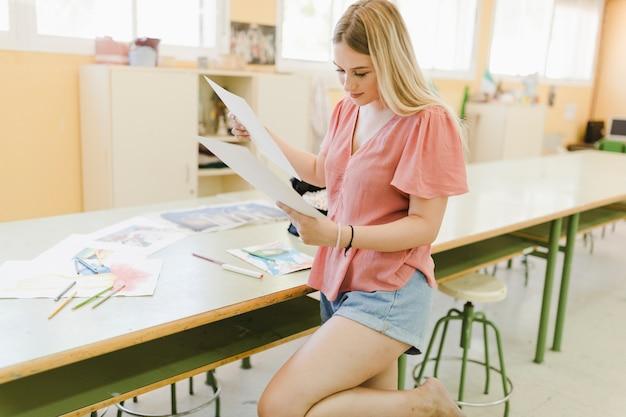 Souriante blonde jeune femme regardant du papier de toile dans l'atelier