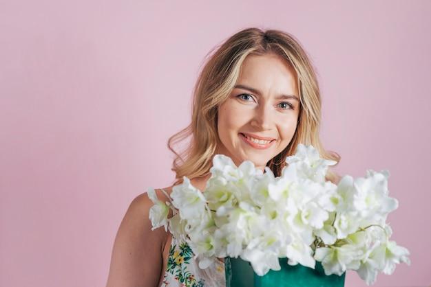 Souriante blonde jeune femme tenant un bouquet de fleurs blanches