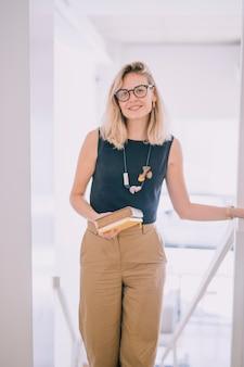 Souriante blonde jeune femme tenant des livres à la main en regardant la caméra