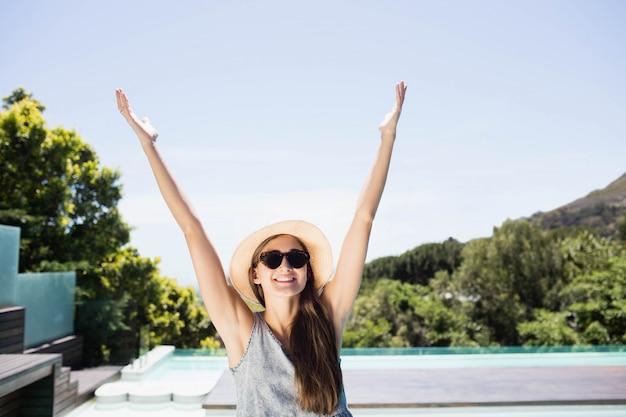 Souriante brune levant les mains au bord de la piscine