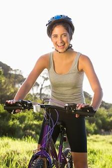 Souriante brunette athlétique assis sur le vélo de montagne