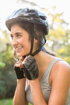 Souriante brunette athlétique mettant sur le casque
