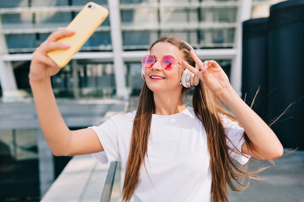 Souriante et dansante jeune femme faisant un selfie avec son smartphone et écoute de la musique au casque