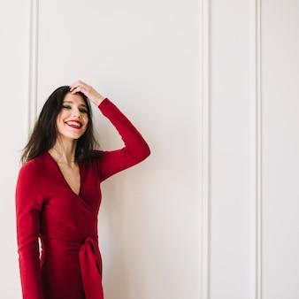 Souriante élégante jeune femme en robe rouge tenant les cheveux dans la chambre