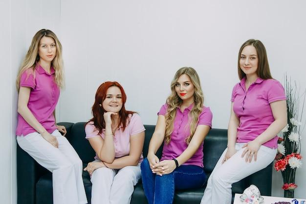 Souriante équipe de quatre maîtres professionnels, administrateur, coiffeuse, esthéticienne accueillant dans un salon de beauté moderne