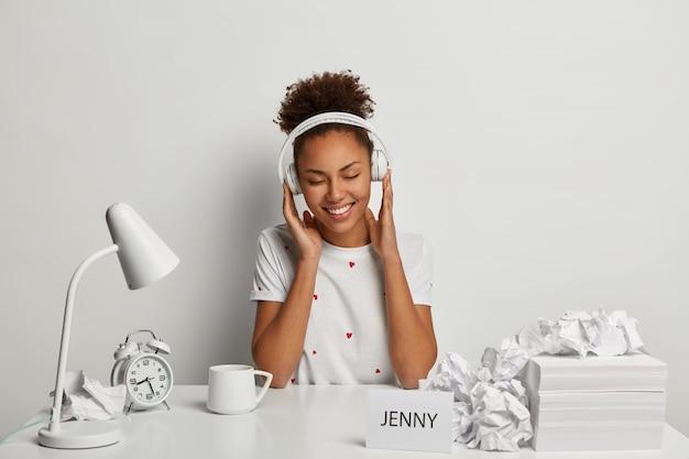 Souriante étudiante à la peau sombre porte des écouteurs stéréo, écoute l'audio