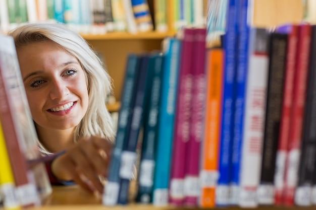Souriante étudiante sélectionnant livre dans la bibliothèque