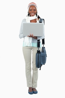 Souriante étudiante en vêtements d'hiver et ordinateur portable