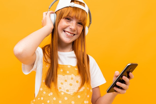 Souriante fille rousse européenne avec un casque rouge et un téléphone