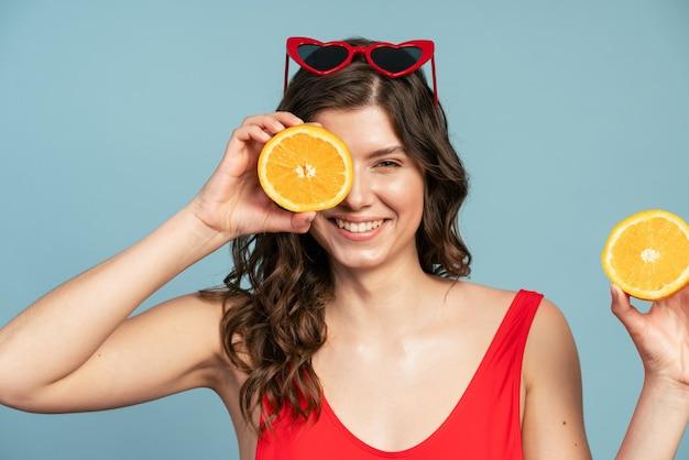 Souriante, gentille fille portant des lunettes sur la tête ferma les yeux avec une demi-orange