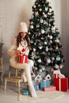 Souriante et heureuse jeune femme en vêtements d'hiver assis confortablement sur le sol près de l'arbre de noël ouvre une boîte-cadeau de noël