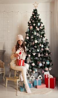 Souriante et heureuse jeune femme en vêtements d'hiver assis confortablement sur le sol près de l'arbre de noël ouvre un cadeau