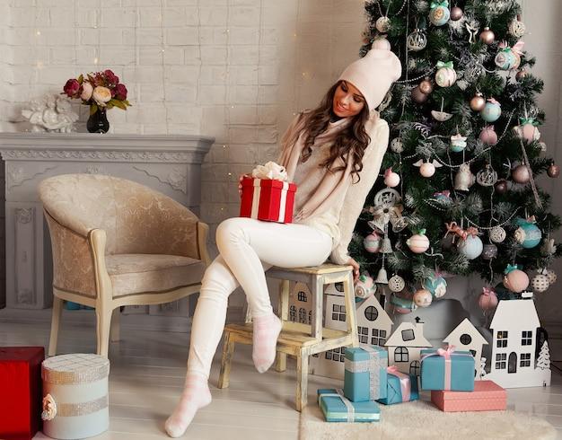 Souriante et heureuse jeune femme en vêtements d'hiver assise confortablement sur le sol près de l'arbre de noël ouvre un cadeau du nouvel an. la jeune fille aime les cadeaux de noël, rencontre le nouvel an et noël.