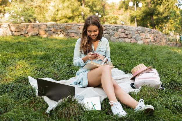 Souriante jeune adolescente portant sur l'herbe dans le parc