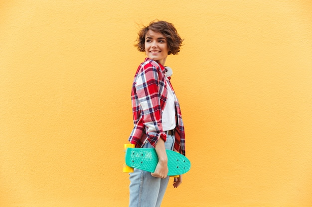 Souriante jeune adolescente tenant une planche à roulettes