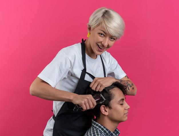 Souriante jeune belle femme barbier en uniforme tenant des outils de barbier et faisant une coupe de cheveux pour garçon isolé sur fond rose