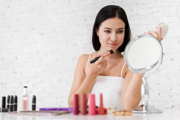 Souriante jeune belle femme peau fraîche et saine tenant des pinceaux de maquillage avec des cosmétiques à la maison.beauté du visage et concept cosmétique