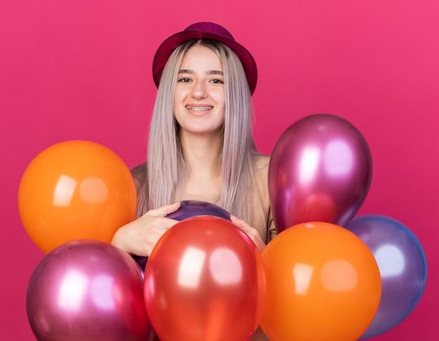 Souriante jeune belle femme portant un chapeau de fête avec des appareils dentaires debout derrière des ballons isolés sur un mur rose