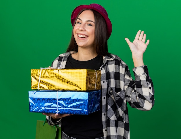 Souriante jeune belle femme portant un chapeau de fête tenant des coffrets cadeaux avec un sac cadeau montrant un geste de bonjour isolé sur un mur vert