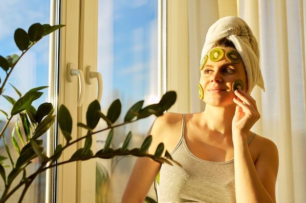 Souriante jeune belle femme se bouchent à la maison près de la fenêtre avec un masque facial aux fruits faits maison naturels de kiwi sur le visage, une serviette sur la tête. soins de la peau, cosmétiques, cosmétologie, dermatologie.
